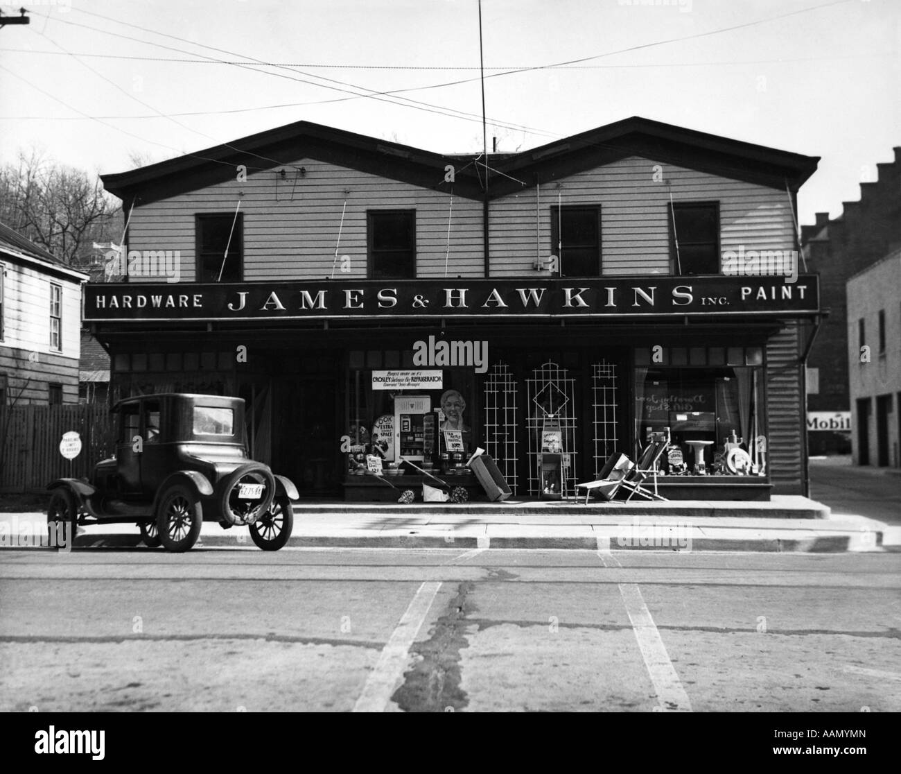 1920s FACADE OF HARDWARE STORE SINGLE CAR PARKED ON STREET IN FRONT - Stock Image