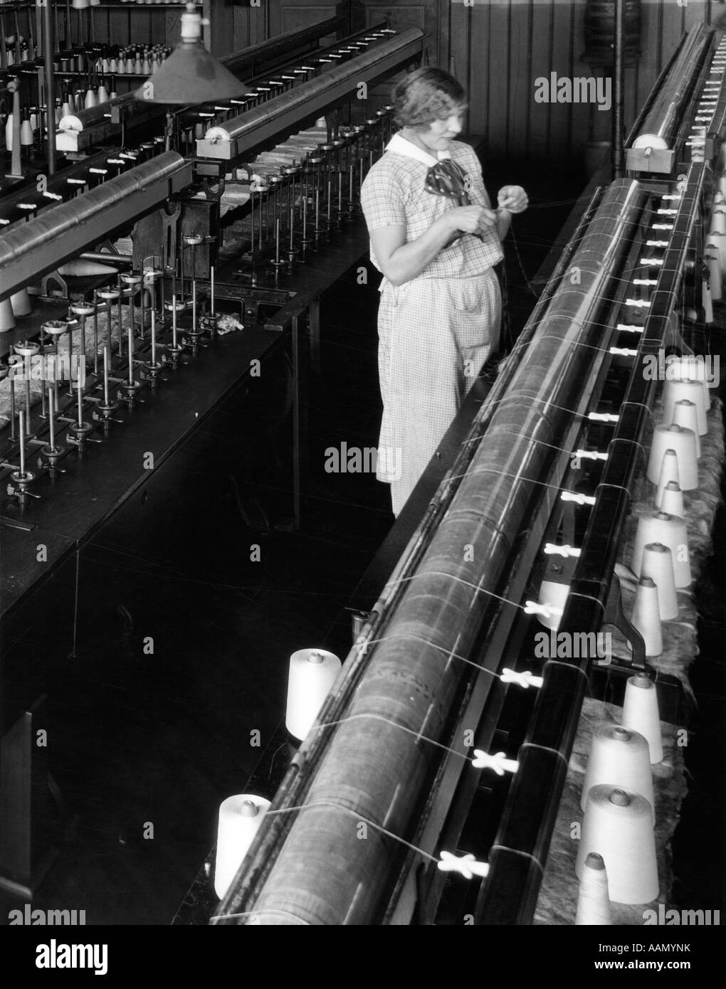 1920s 1930s WOMAN WORKER THREADING BOBBIN INDUSTRIAL SILK WINDING FACTORY PHILADELPHIA PA MACHINE TEXTILE SPOOLS - Stock Image
