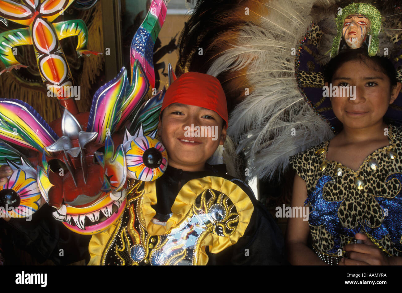 A boy and girl try on costumes at a rental shop in  Oruro Bolivia in preparation for their city s  annual Carnival celebration - Stock Image