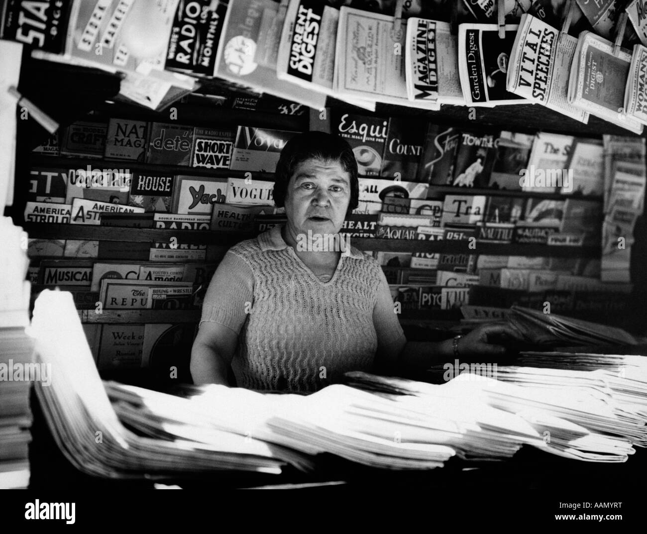 1930s WOMAN SELLING MAGAZINES NYC SIDEWALK NEWSSTAND NEWS STAND NEWSPAPERS 42ND STREET MADISON AVENUE NEW YORK CITY - Stock Image