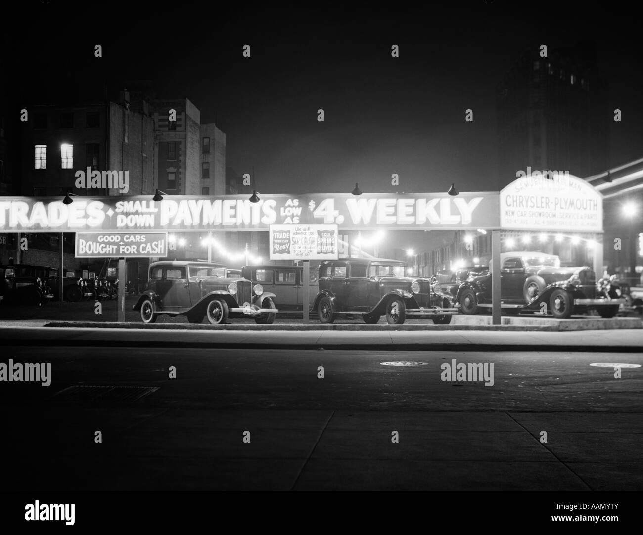 1930s NEW AND USED CAR LOT NIGHT NEW YORK CITY GREENWICH VILLAGE AUTO AUTOMOTIVE AUTOMOBILE SALES SIXTH AVENUE AND - Stock Image