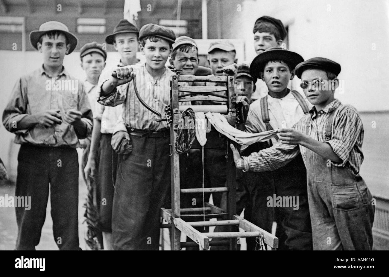 1930s GROUP OF CITY BOYS CRANKING WET LAUNDRY THROUGH MECHANICAL CLOTHES WRINGER LOOKING AT CAMERA - Stock Image