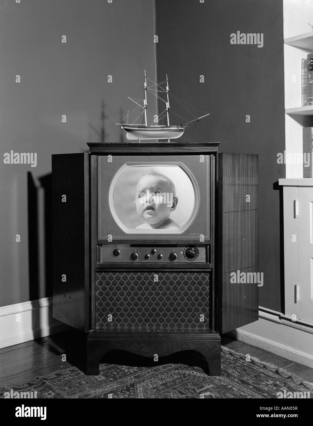1940s 1950s CONSOLE BLACK AND WHITE TELEVISION SET WITH MANY DIALS KNOBS ROOM INTERIOR WITH MODEL SHIP AND ORIENTAL - Stock Image