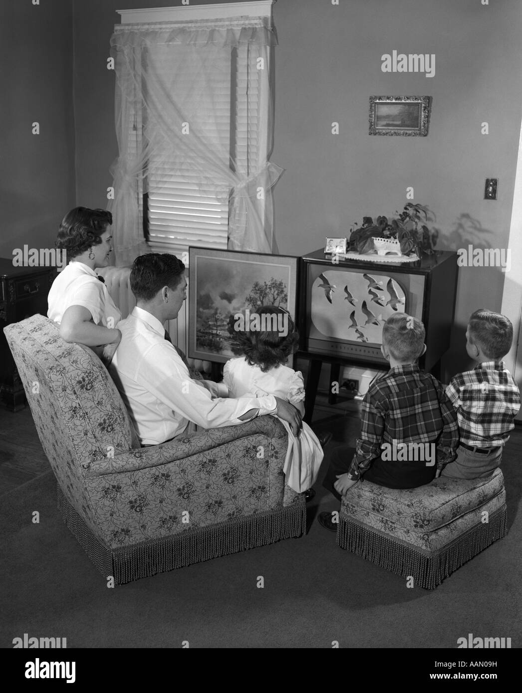 1950s FAMILY WITH 3 CHILDREN WATCHING TV - Stock Image