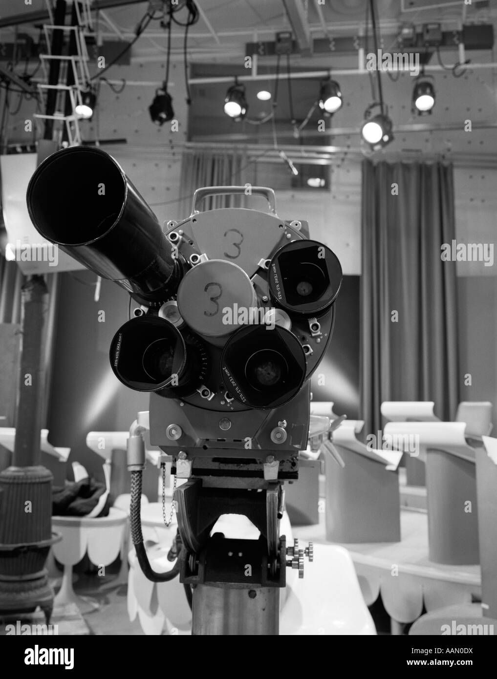 1960s CLOSE-UP OF TV CAMERA LENSES WITH STUDIO SET IN BACKGROUND - Stock Image