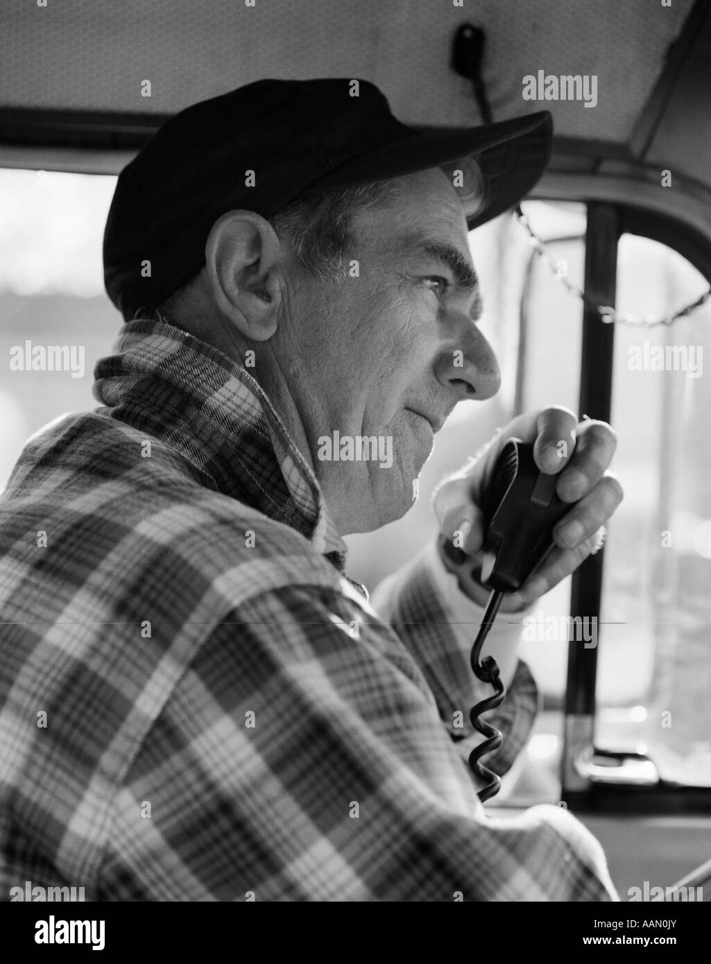 1970s SIDE VIEW OF TRUCKER IN PLAID FLANNEL SHIRT   BASEBALL CAP USING CB  RADIO 07da6e897c7
