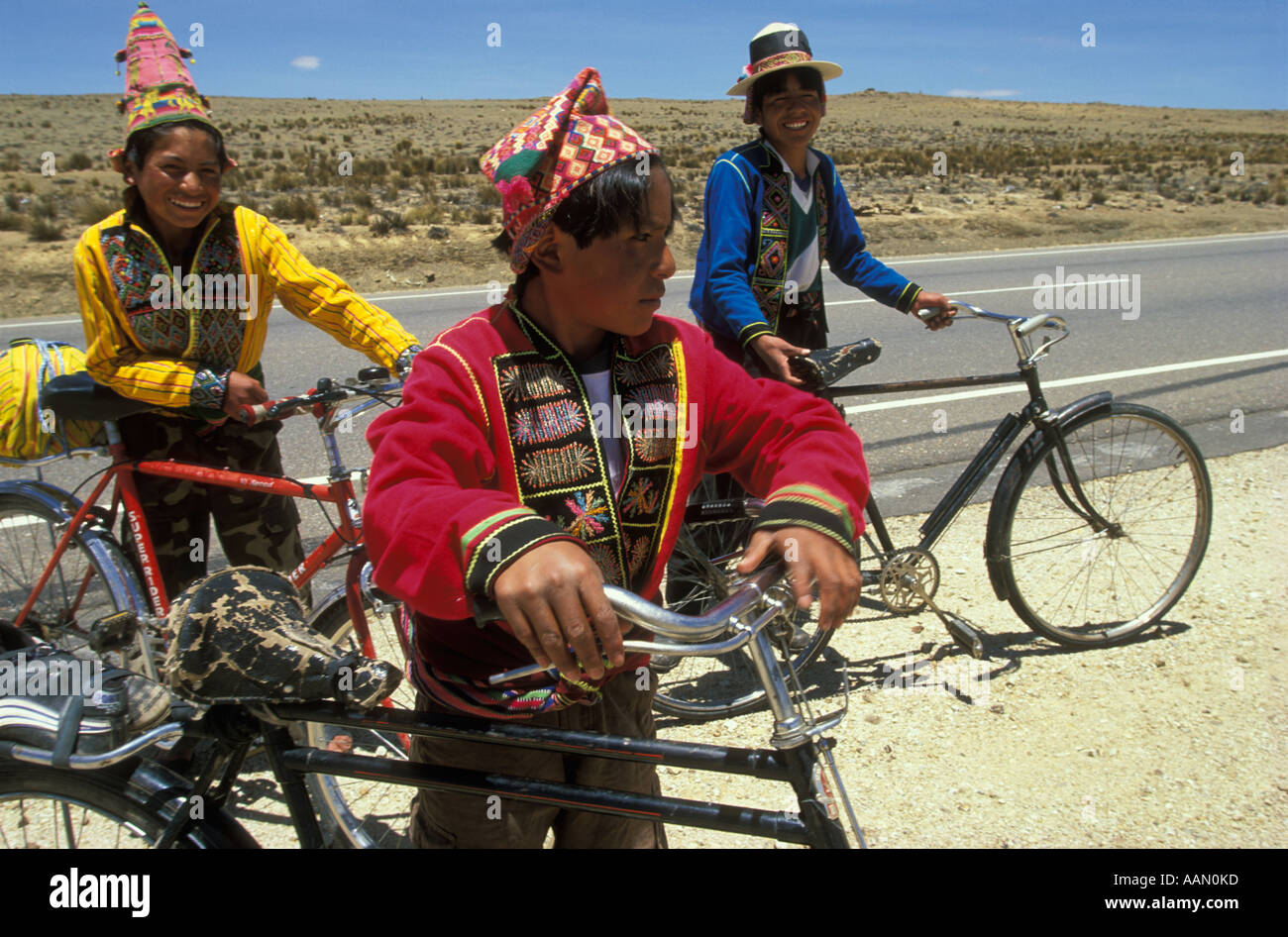 Indian boys wearing traditional dress stand with  their bicycles on a road between Cochabamba  and Oruro in the Bolivian Andes - Stock Image