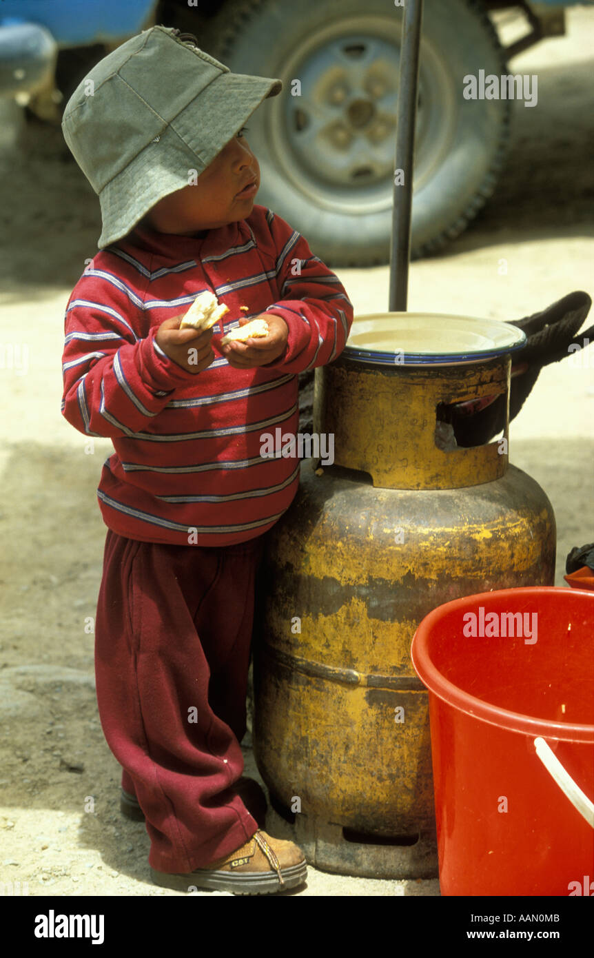 A Bolivian Indian boy in Oruro Department stands next to a gas tank  with a snack in his hands Bolivia - Stock Image