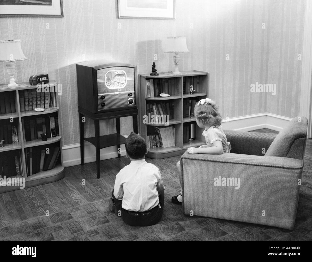 1940s 1950s BOY AND GIRL WITH BACKS TO VIEWER IN LIVING ROOM WATCHING A  SMALL SCREEN