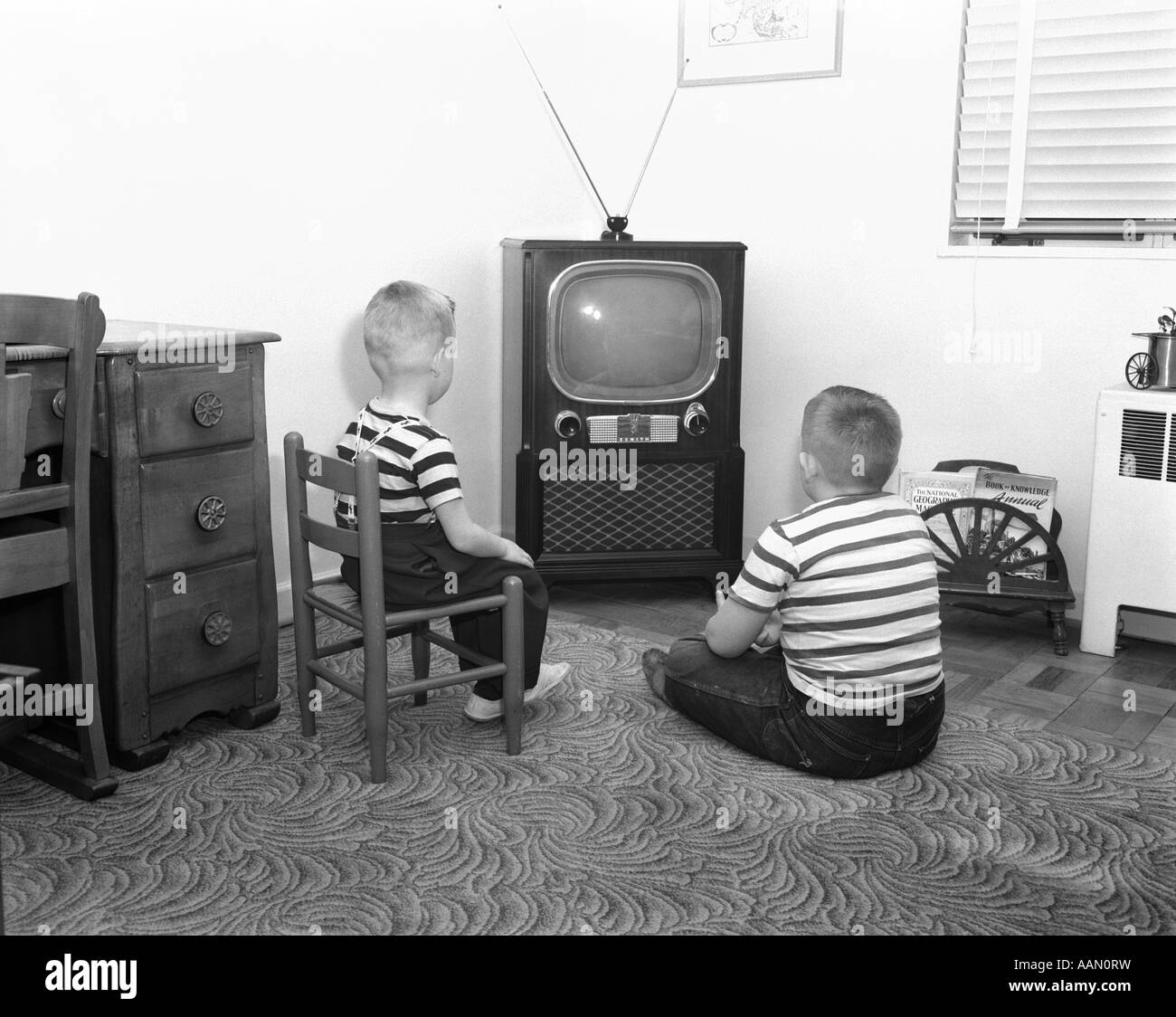 1950s BACK VIEW OF 2 BOYS IN STRIPED T-SHIRTS WATCHING TV - Stock Image
