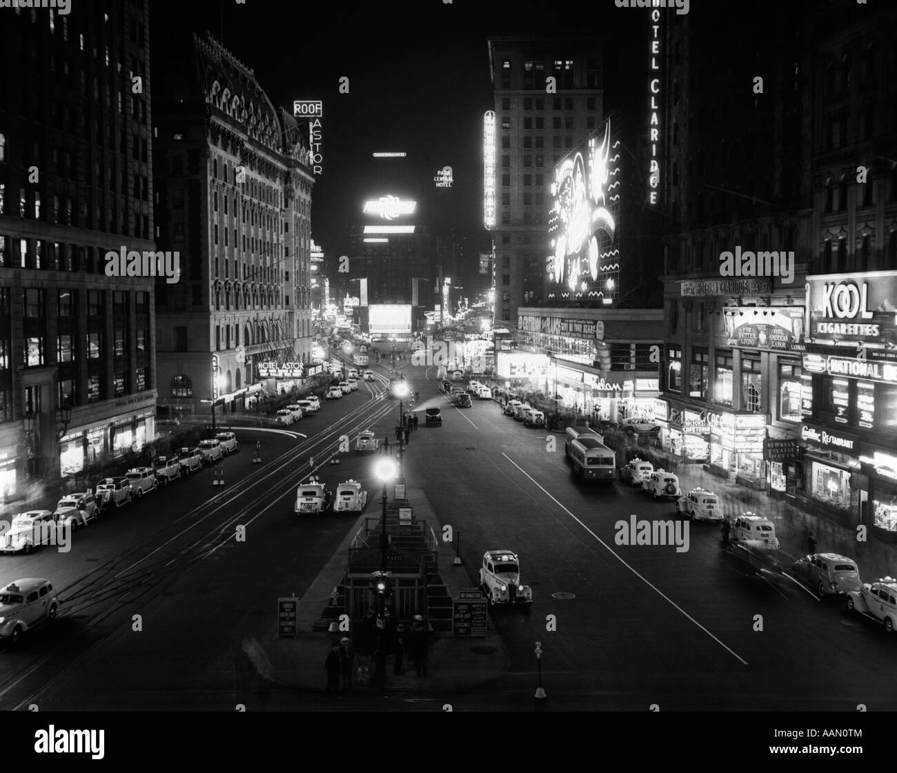 1930s OVERHEAD OF TIMES SQUARE LIT UP AT NIGHT WITH CARS LINING CURBS - Stock Image