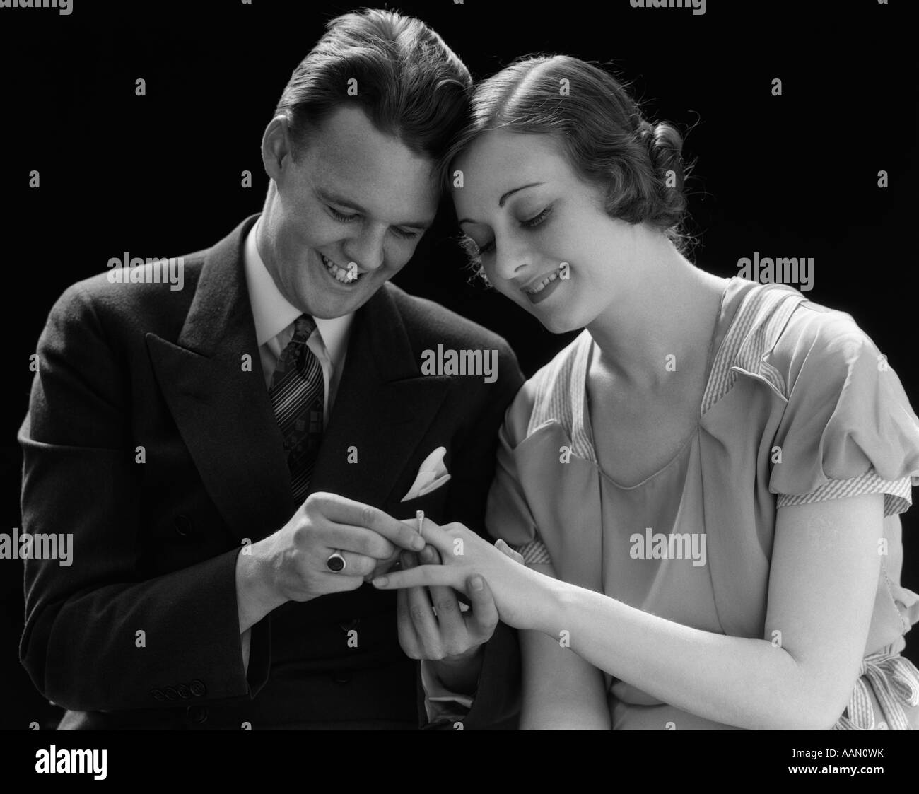 1930s SMILING COUPLE SITTING HEADS PRESSED TOGETHER MAN PUTTING ENGAGEMENT RING ON WOMAN'S FINGER - Stock Image