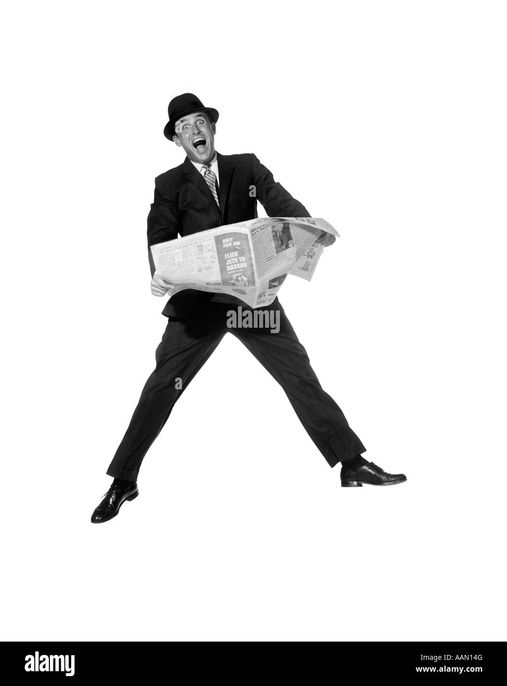 1950s MAN IN BUSINESS SUIT AND HAT HOLDING NEWSPAPER WITH EXAGGERATED EXPRESSION - Stock Image