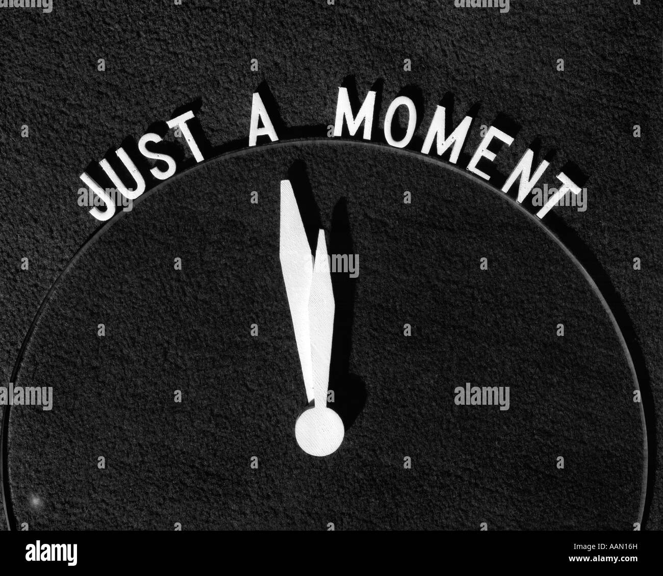 SIGN JUST A MOMENT CLOCK - Stock Image