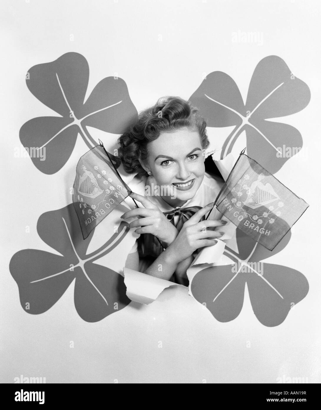 1950s SMILING WOMAN HEAD THROUGH BACKDROP SURROUNDED BY 4 SHAMROCKS HOLDING ERIN GO BRAGH FLAGS IRISH HOLIDAY ST. - Stock Image