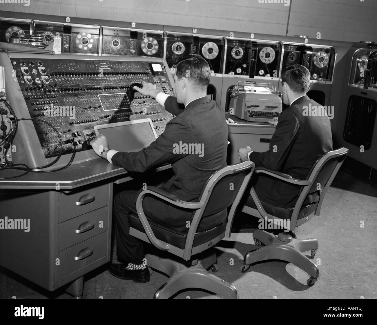 1950s 1960s UNIVAC COMPUTER ROOM WITH TWO MEN WORKING AT CONSOLE AND TYPEWRITER KEYBOARD - Stock Image