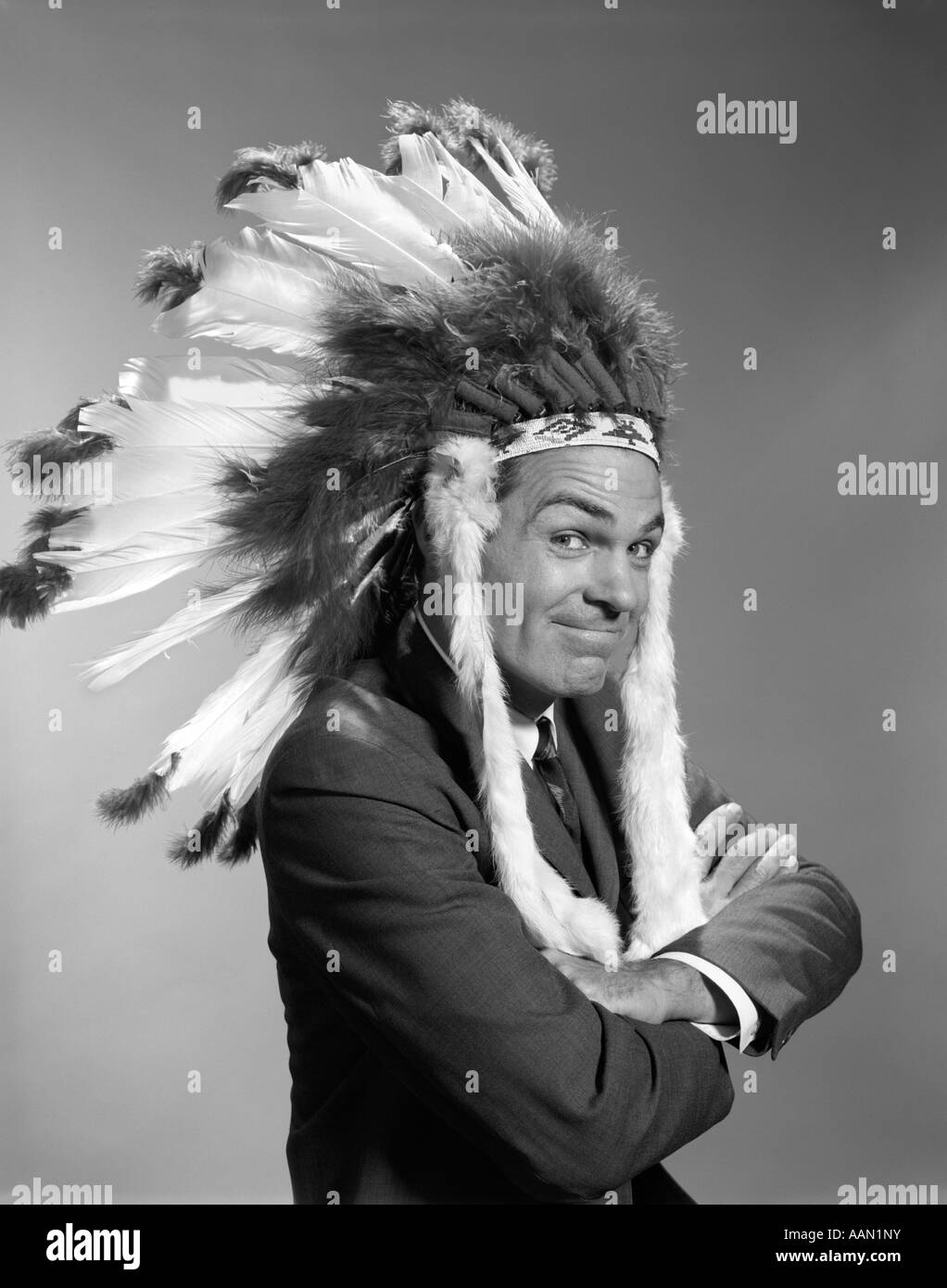 1960s PORTRAIT MAN WEARING INDIAN CHIEF FEATHERED HEADDRESS - Stock Image