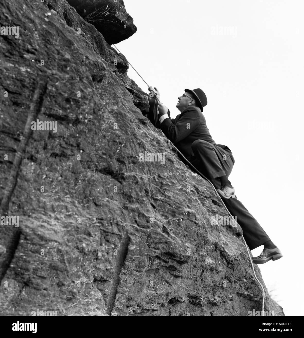 1960s BUSINESSMAN IN HAT & SUIT CLIMBING ROCK HOLDING ROPE - Stock Image