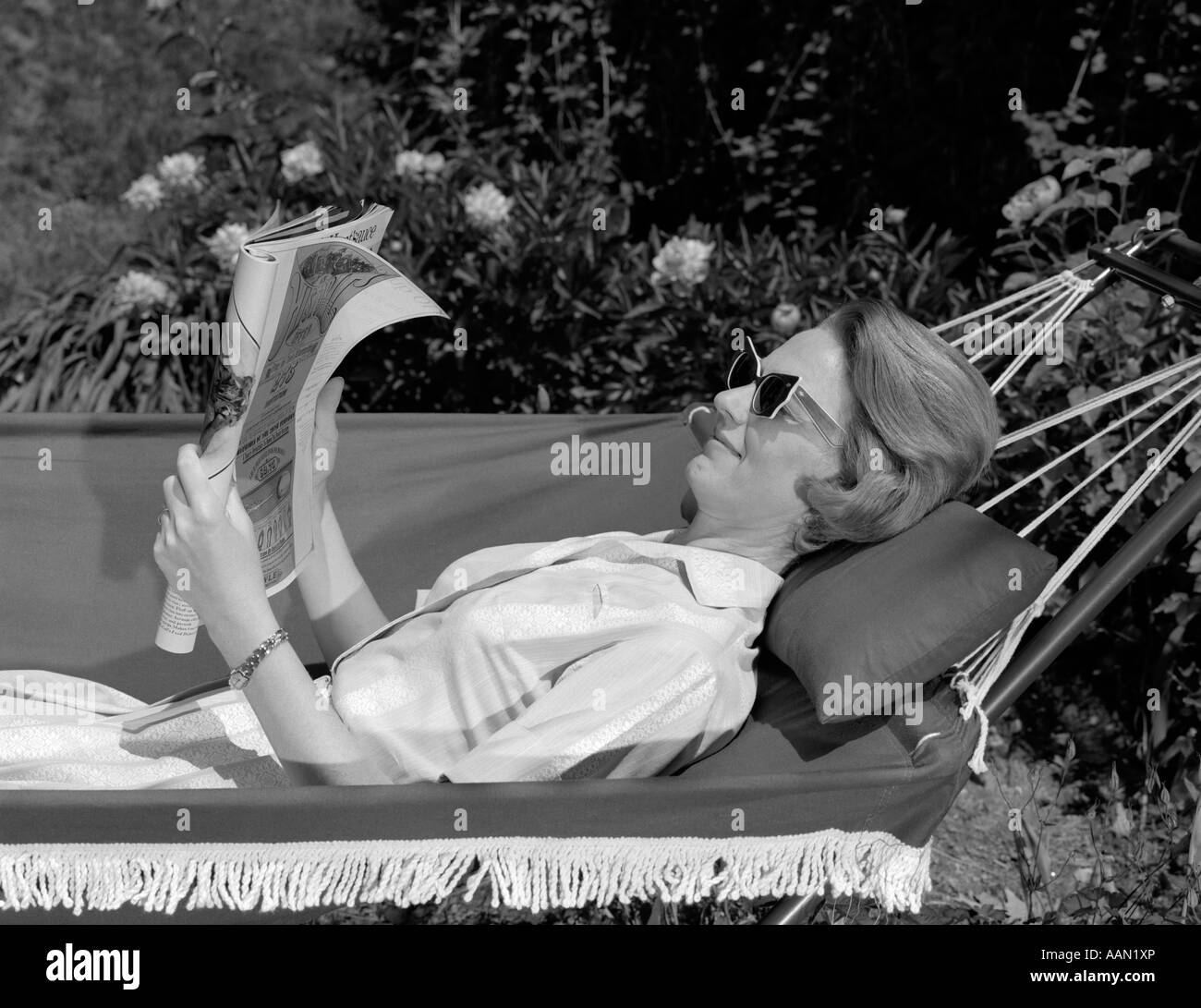 1960s SIDE VIEW OF WOMAN WEARING SUNGLASSES LYING IN FRINGED HAMMOCK READING MAGAZINE - Stock Image