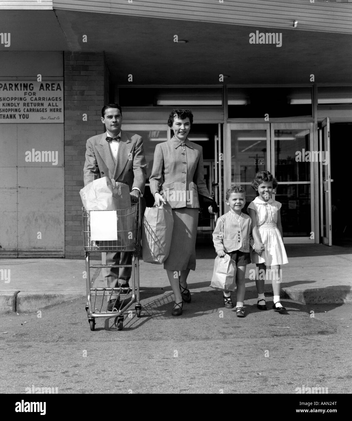 1950s FAMILY MAN WOMAN GIRL BOY WALKING OUT OF SUPERMARKET STORE MOTHER AND SON CARRYING BAGS FATHER PUSHING GROCERY - Stock Image