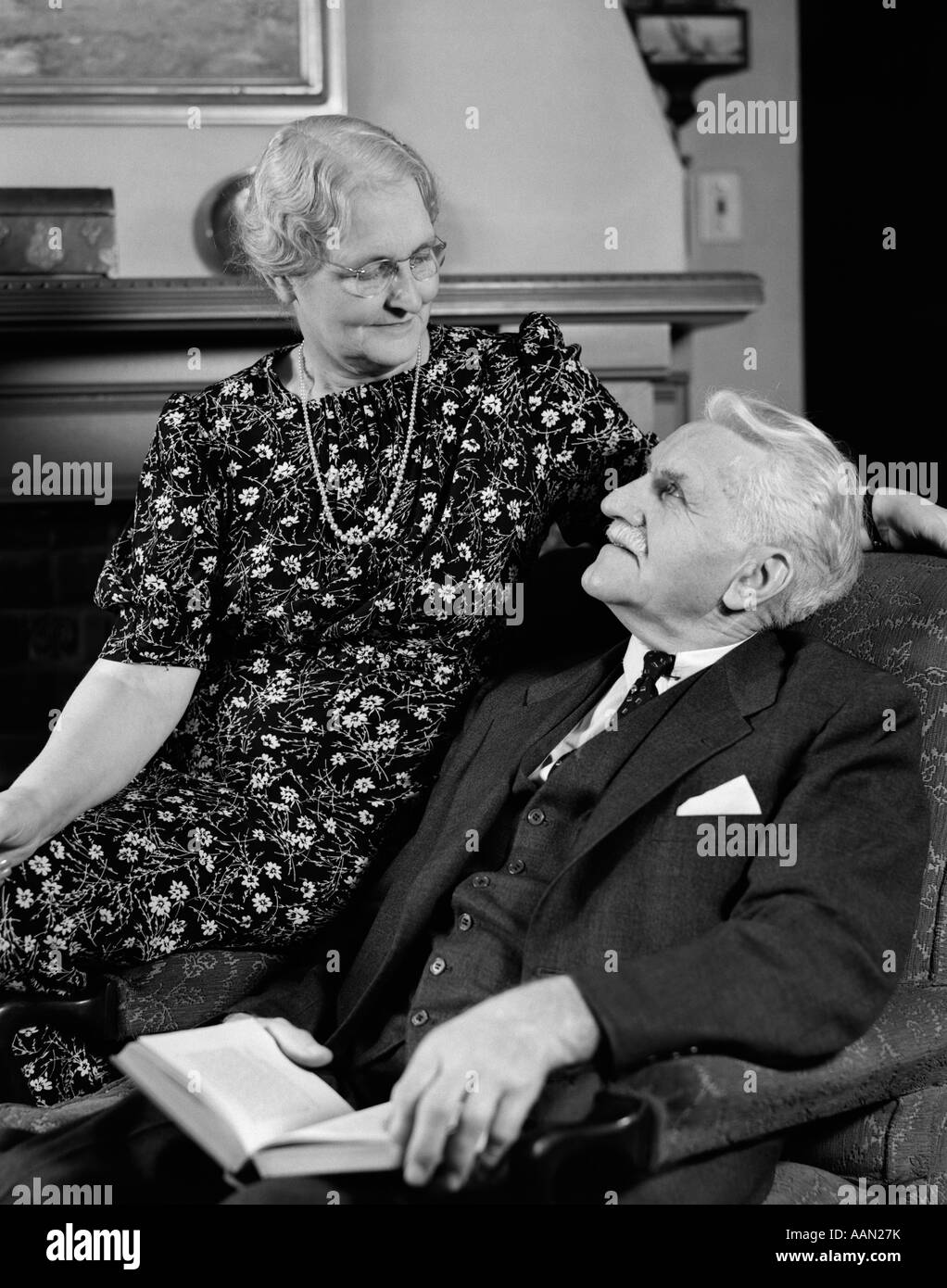 1940s ELDERLY COUPLE SITTING IN CHAIR LOOKING AT EACH OTHER - Stock Image