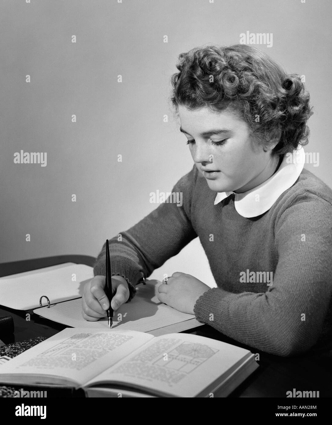 1940s YOUNG GIRL IN SCHOOL UNIFORM STUDYING AT DESK WITH BOOKS AND NOTES - Stock Image