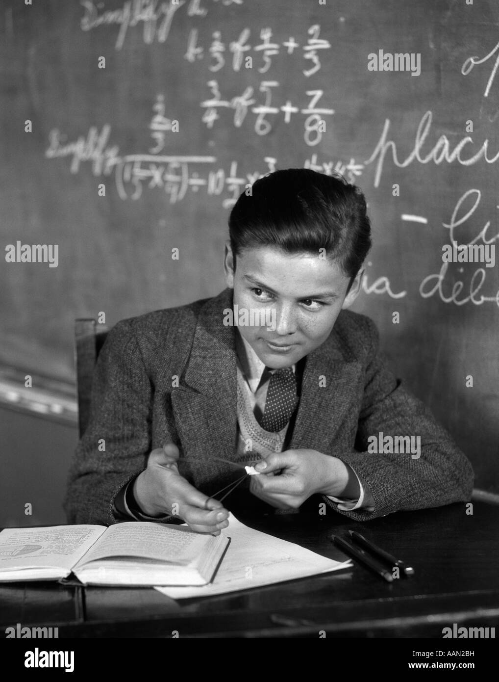 1920s 1930s BOY AT DESK IN CLASSROOM IN FRONT OF BLACKBOARD SHOOTING PAPER WAD WITH RUBBER BAND - Stock Image