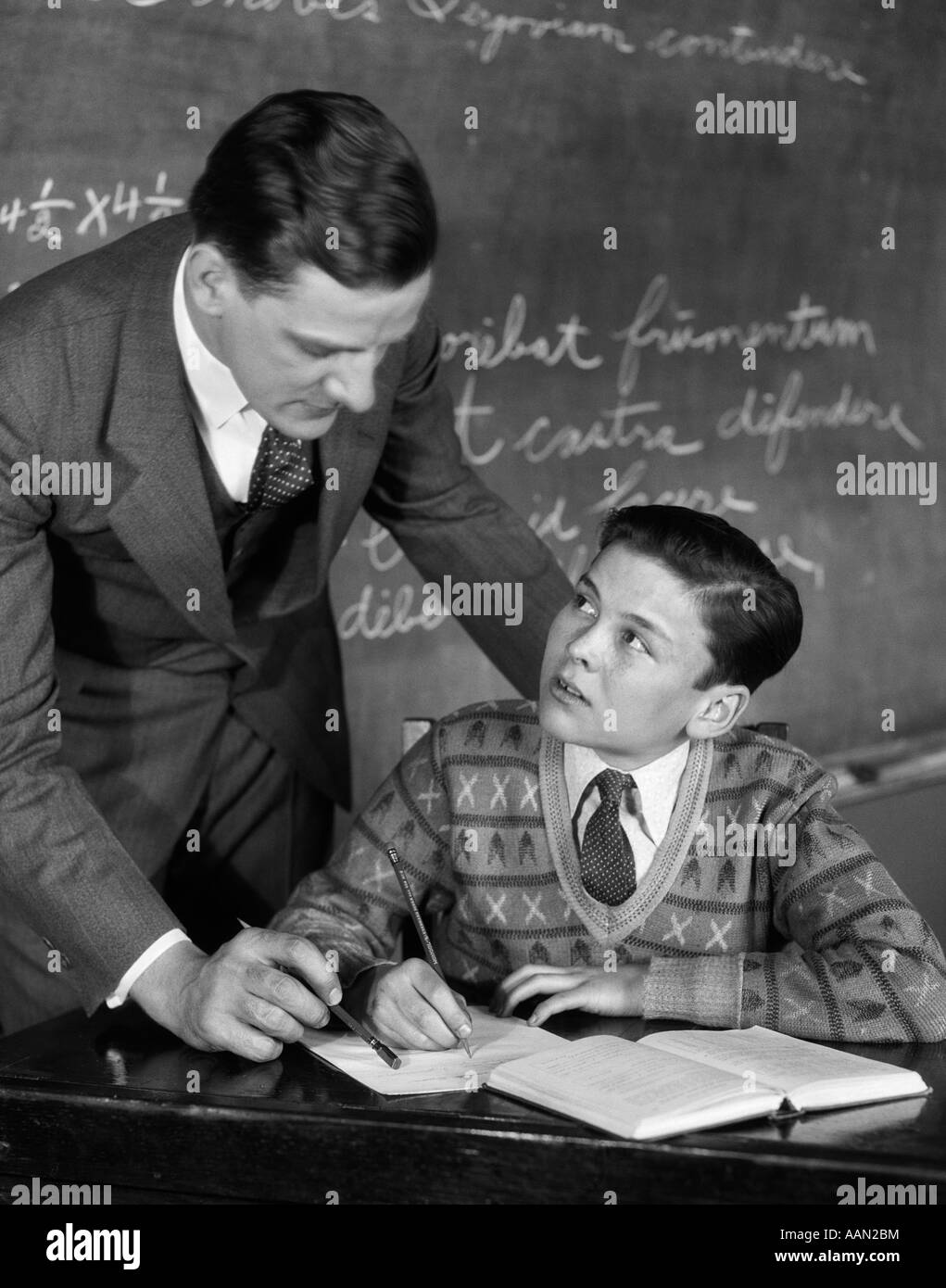 1920s CLASSROOM MALE TEACHER HELPING BOY AT DESK - BLACKBOARD IN BACKGROUND - Stock Image