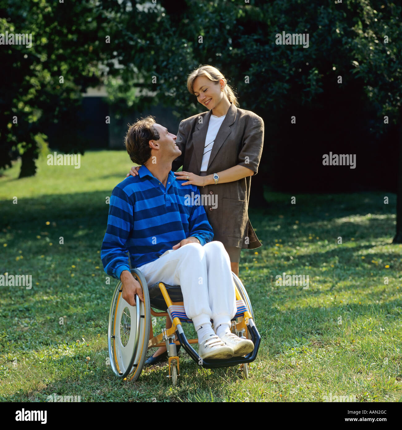 Disabled man in wheelchair and woman in garden - Stock Image