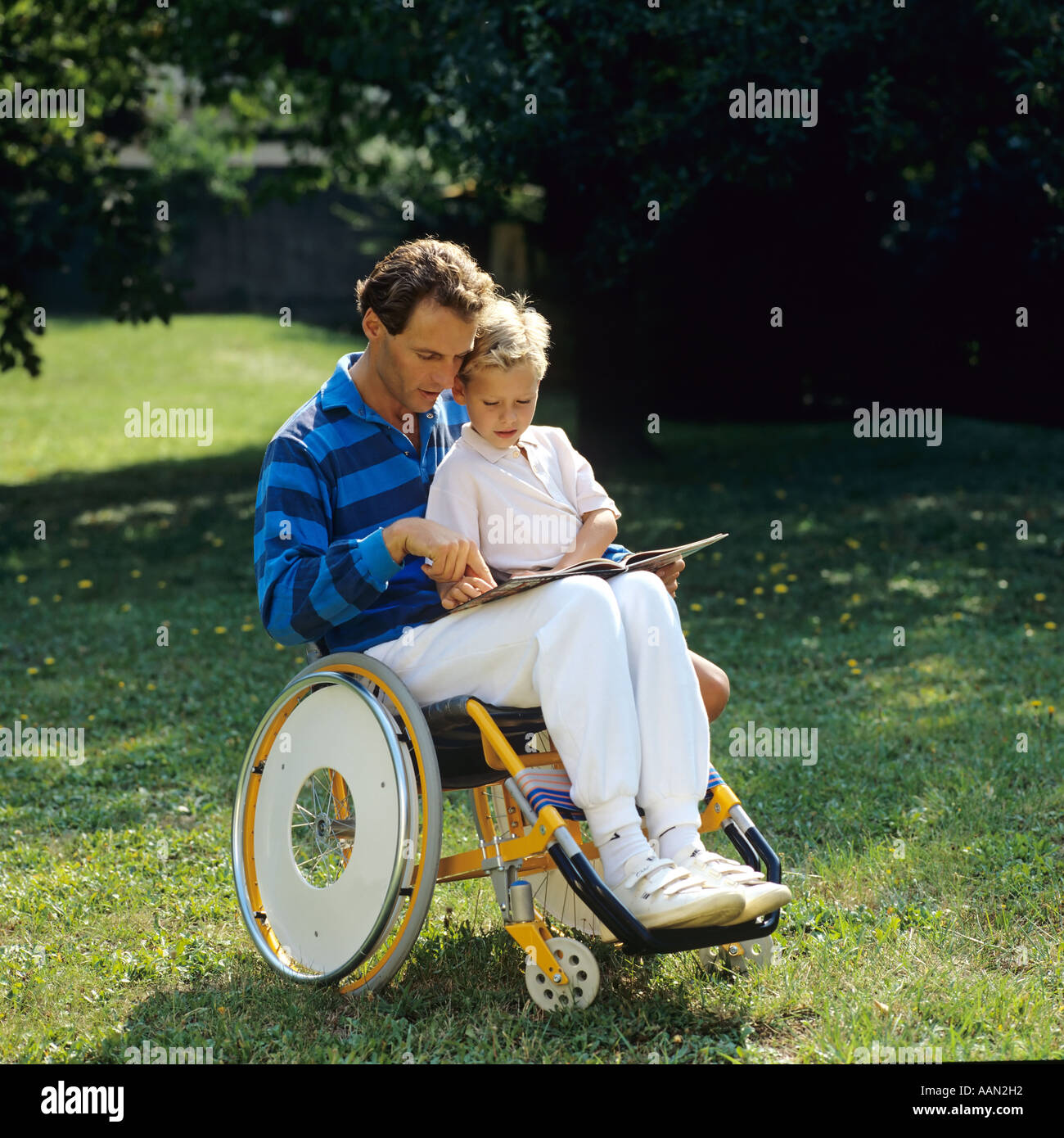 Disabled man in wheelchair reading book to little boy in garden - Stock Image