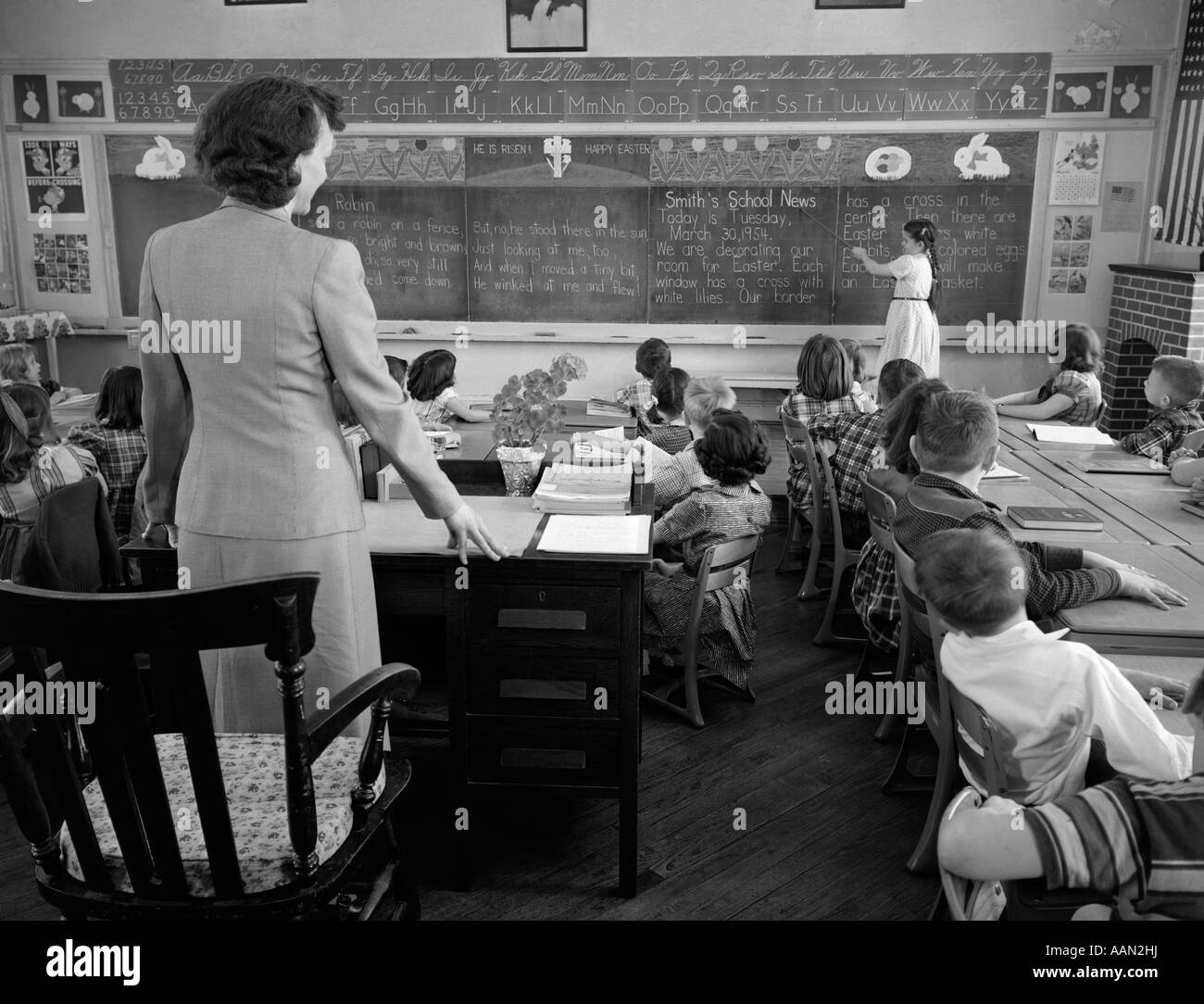 1950s GIRL AT FRONT OF CLASSROOM USING POINTER TO READ THROUGH SCHOOL NEWS ON CHALKBOARD WITH TEACHER STANDING AT Stock Photo