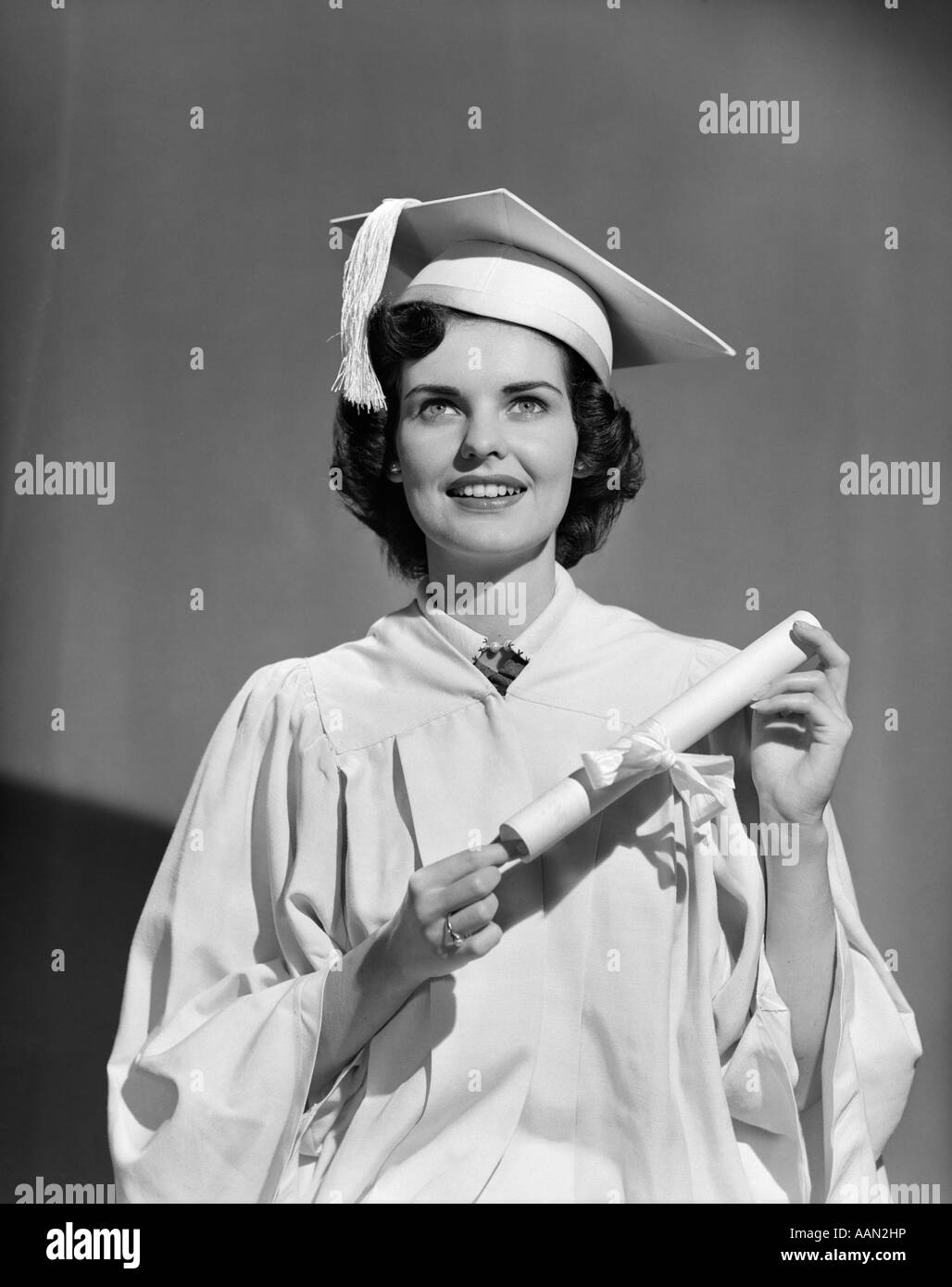 1950s WOMAN TEEN GIRL WHITE CAP GOWN HOLDING GRADUATION DIPLOMA - Stock Image