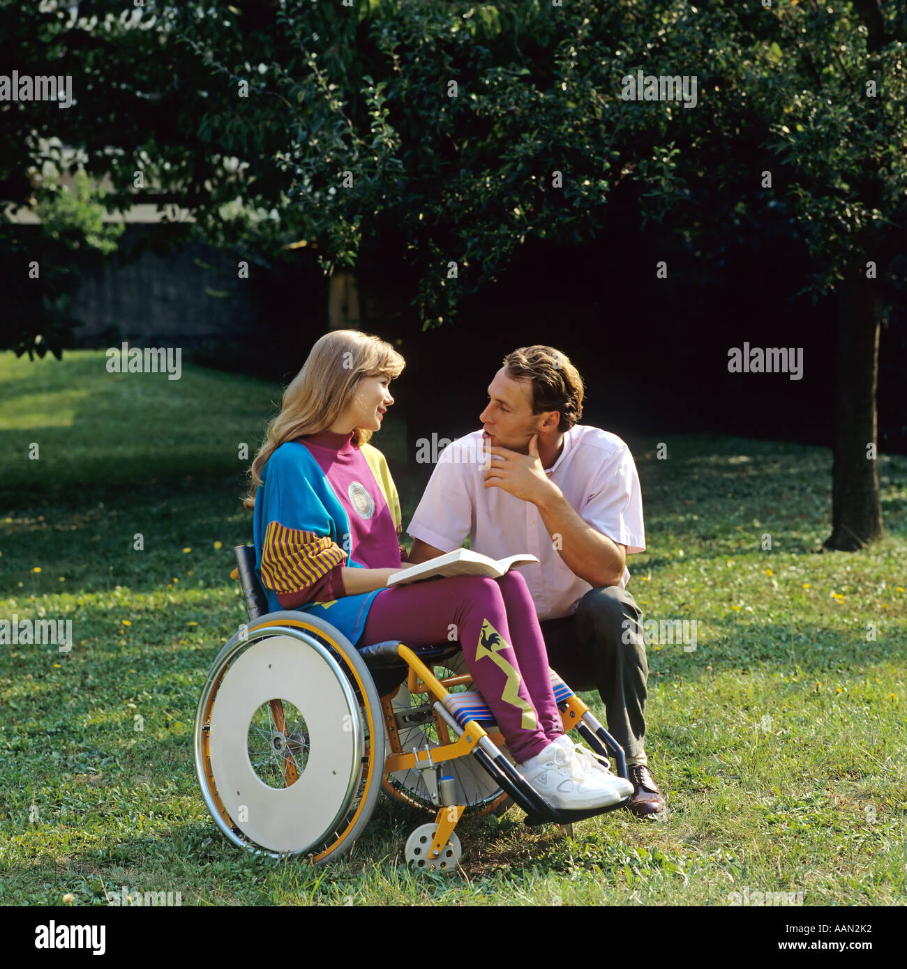 Disabled woman in wheelchair and man in garden - Stock Image