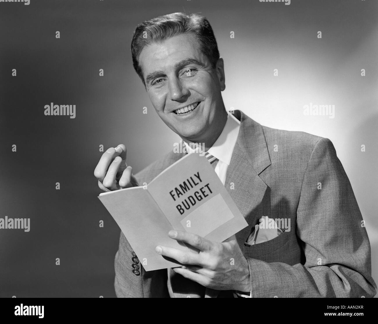 1950s SMILING MAN IN SUIT HOLDING FAMILY BUDGET BOOKLET LOOKING AT CAMERA - Stock Image