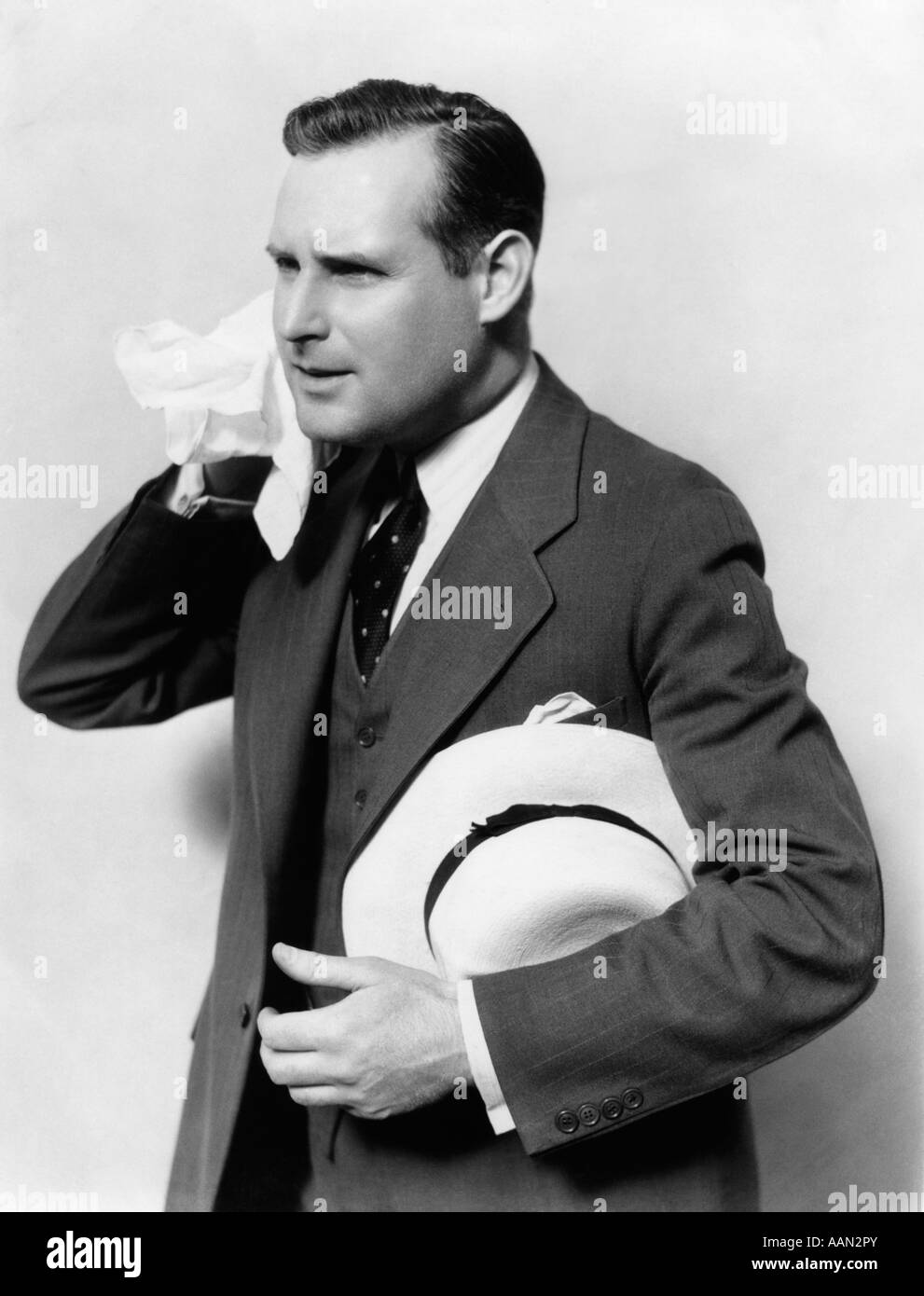 1930s MAN IN SUIT HOLDING HAT WIPING FACE WITH HANDKERCHIEF - Stock Image