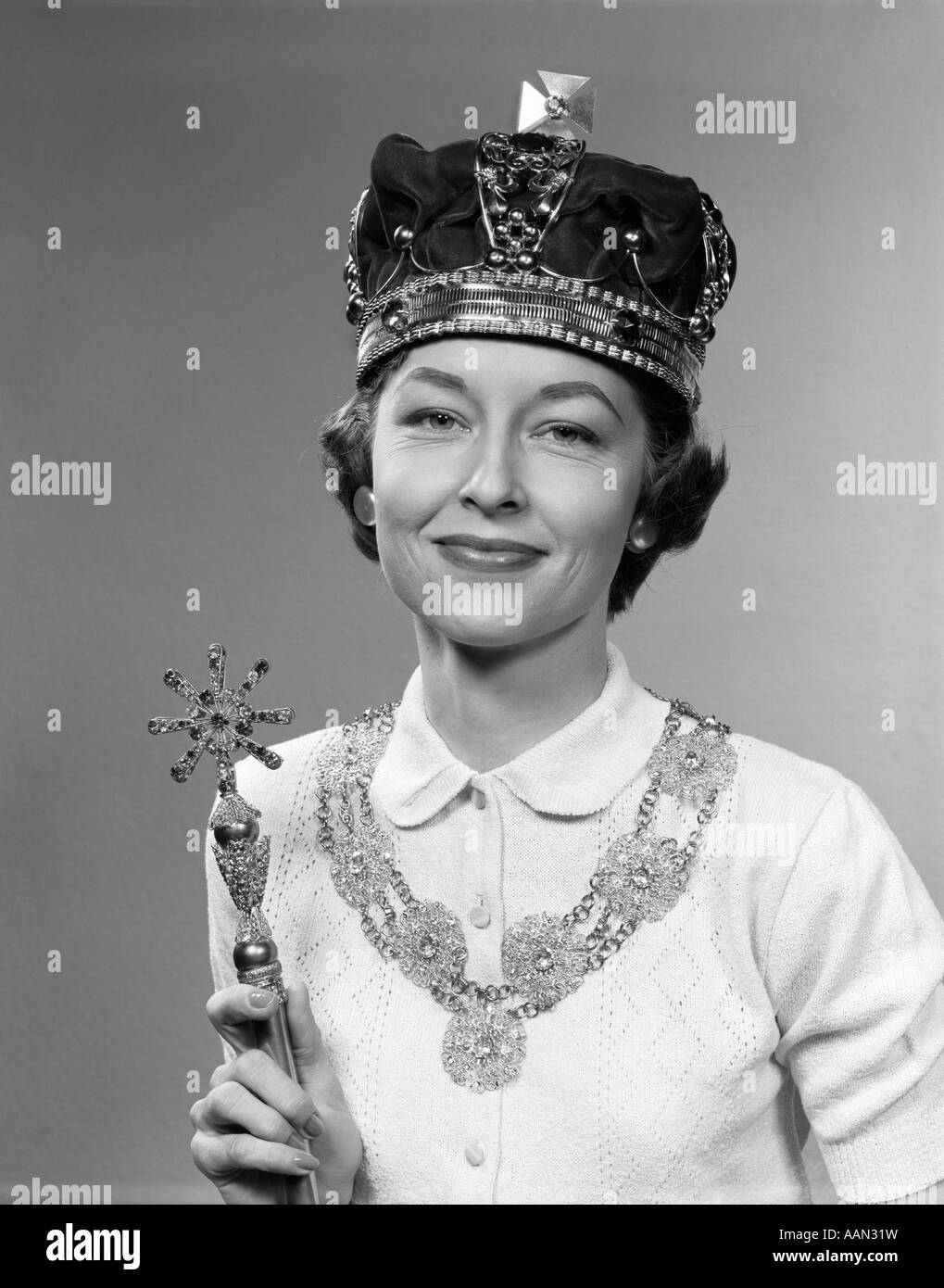 1950s QUEEN FOR A DAY WOMAN WEARING ROYAL CROWN HOLDING SCEPTER LOOKING AT CAMERA - Stock Image