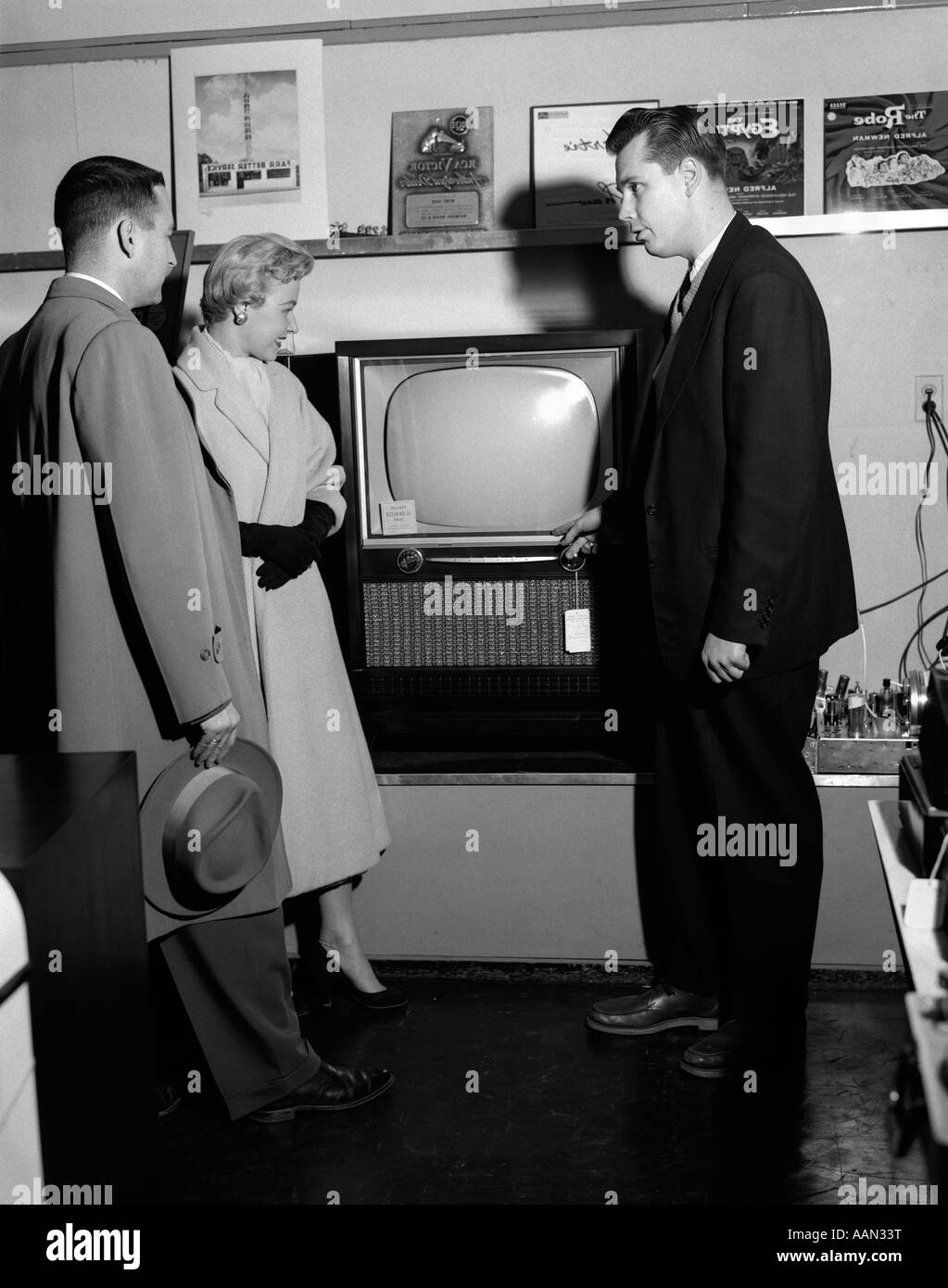 1950s COUPLE WITH SALESMAN IN ELECTRIC APPLIANCE STORE SHOPPING FOR TELEVISION - Stock Image