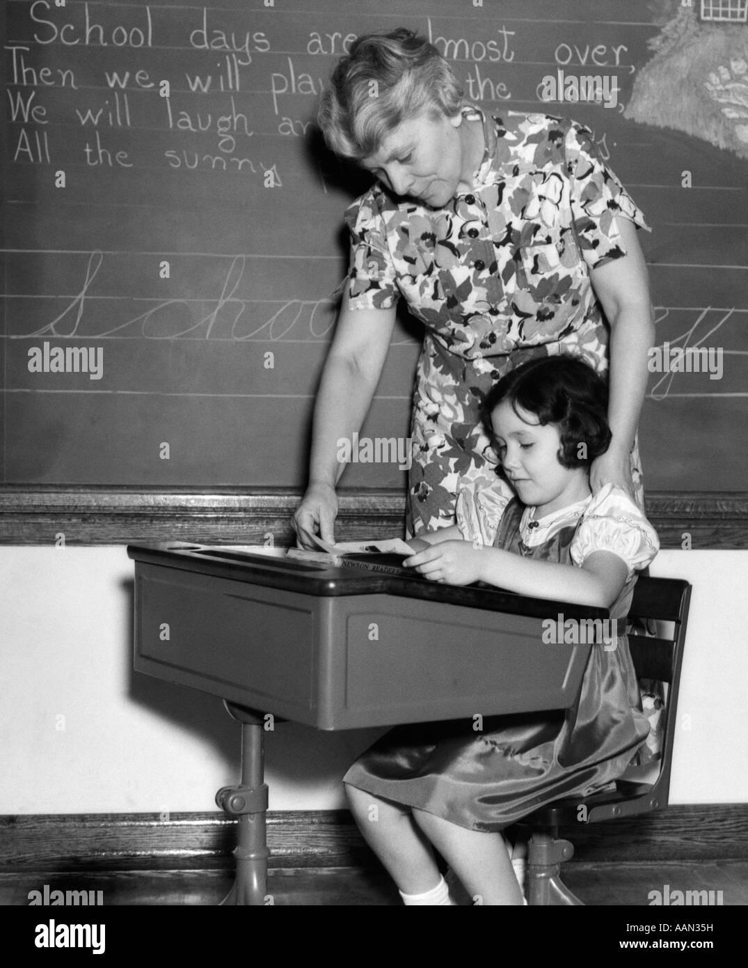 1930s FEMALE TEACHER IN FRONT OF BLACKBOARD HELPING GIRL STUDENT AT DESK READING BOOK - Stock Image
