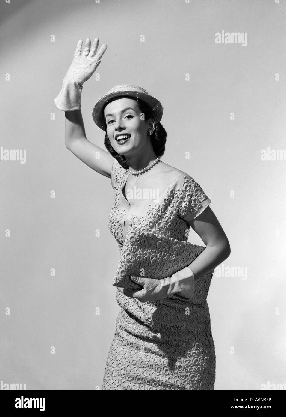 1950s WOMAN DRESSED UP WEARING GLOVES HAT AND HOLDING MATCHING  PURSE WAVING LOOKING AT CAMERA Stock Photo