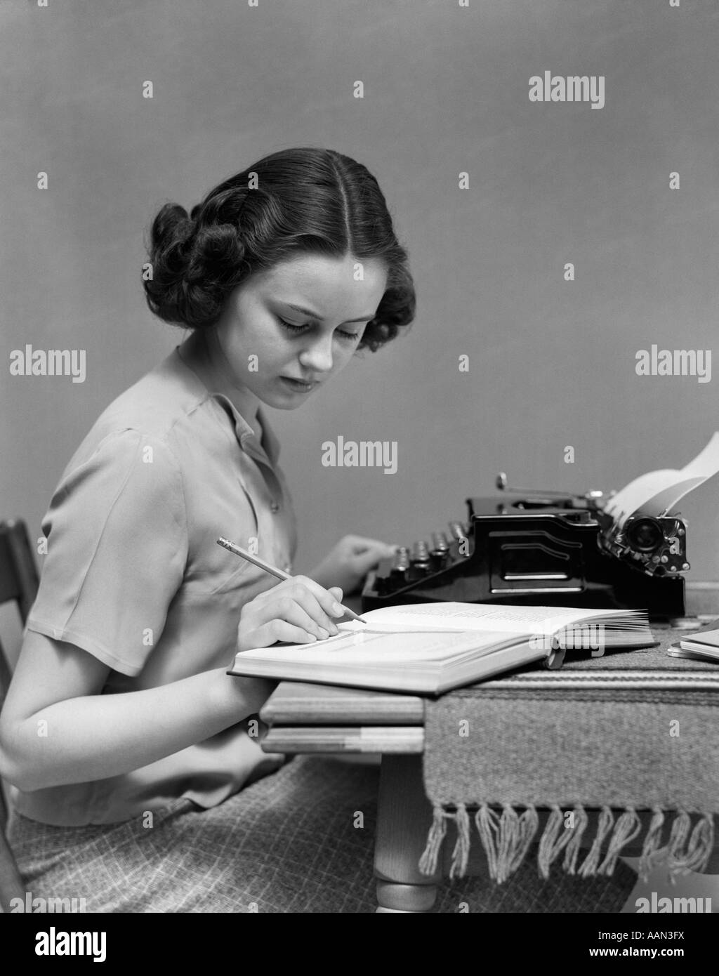 1930s YOUNG WOMAN STUDENT SITTING AT TABLE WITH TYPEWRITER AND BOOK STUDYING - Stock Image