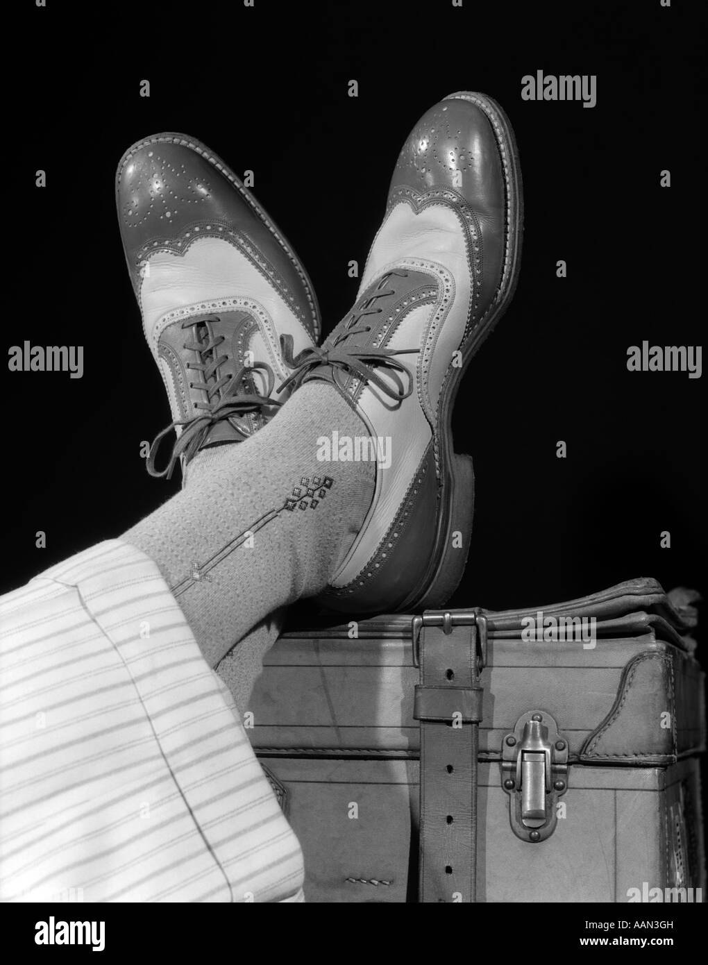 1930s 1940s CROSSED FEET OF A MAN WEARING TWO TONE WING TIP SPECTATOR SHOES SILK SOCKS AND STRIPED WHITE WOOL CUFFED - Stock Image