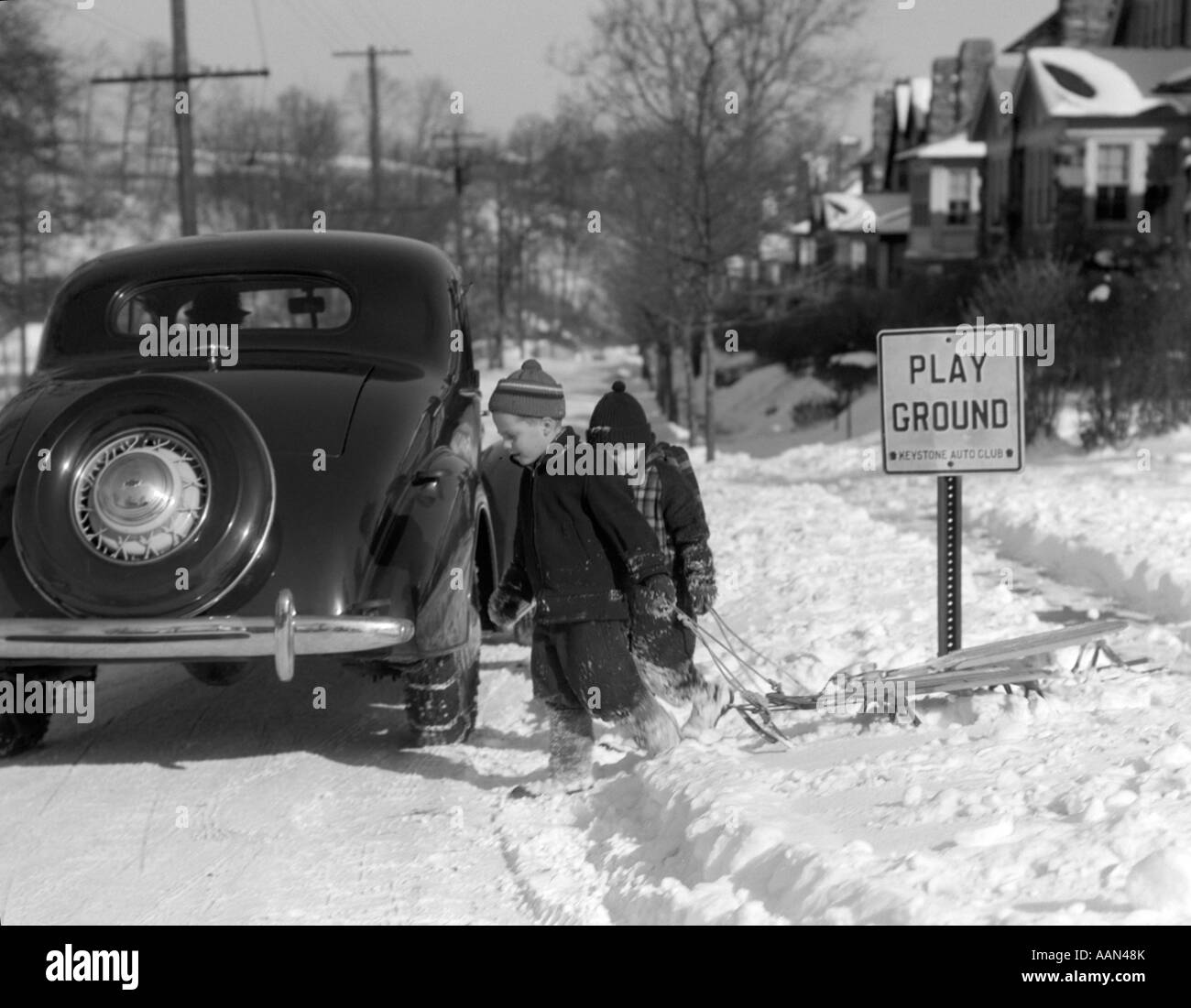 1940s TWO BOYS PULLING SLEDS ACROSS A SNOWY SUBURBAN WINTER STREET WITH PARKED CAR AND SIGN THAT SAYS PLAY GROUND - Stock Image