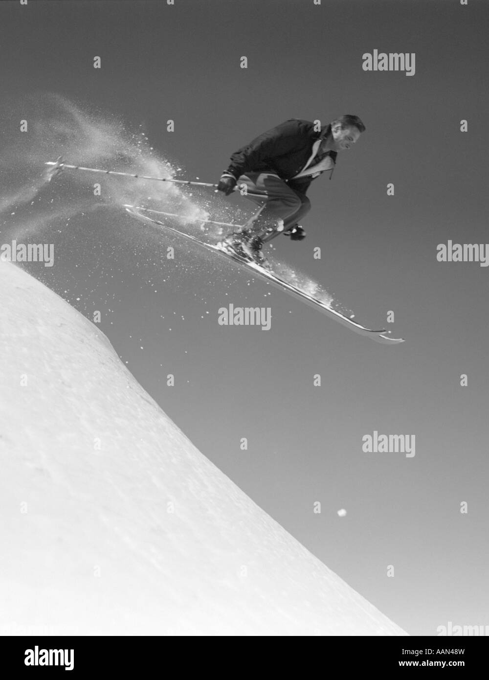 1950s MAN SKIING DOWNHILL OFF SLOPE JUMPING INTO AIR SKI SKIS SPORTS WINTER SNOW - Stock Image