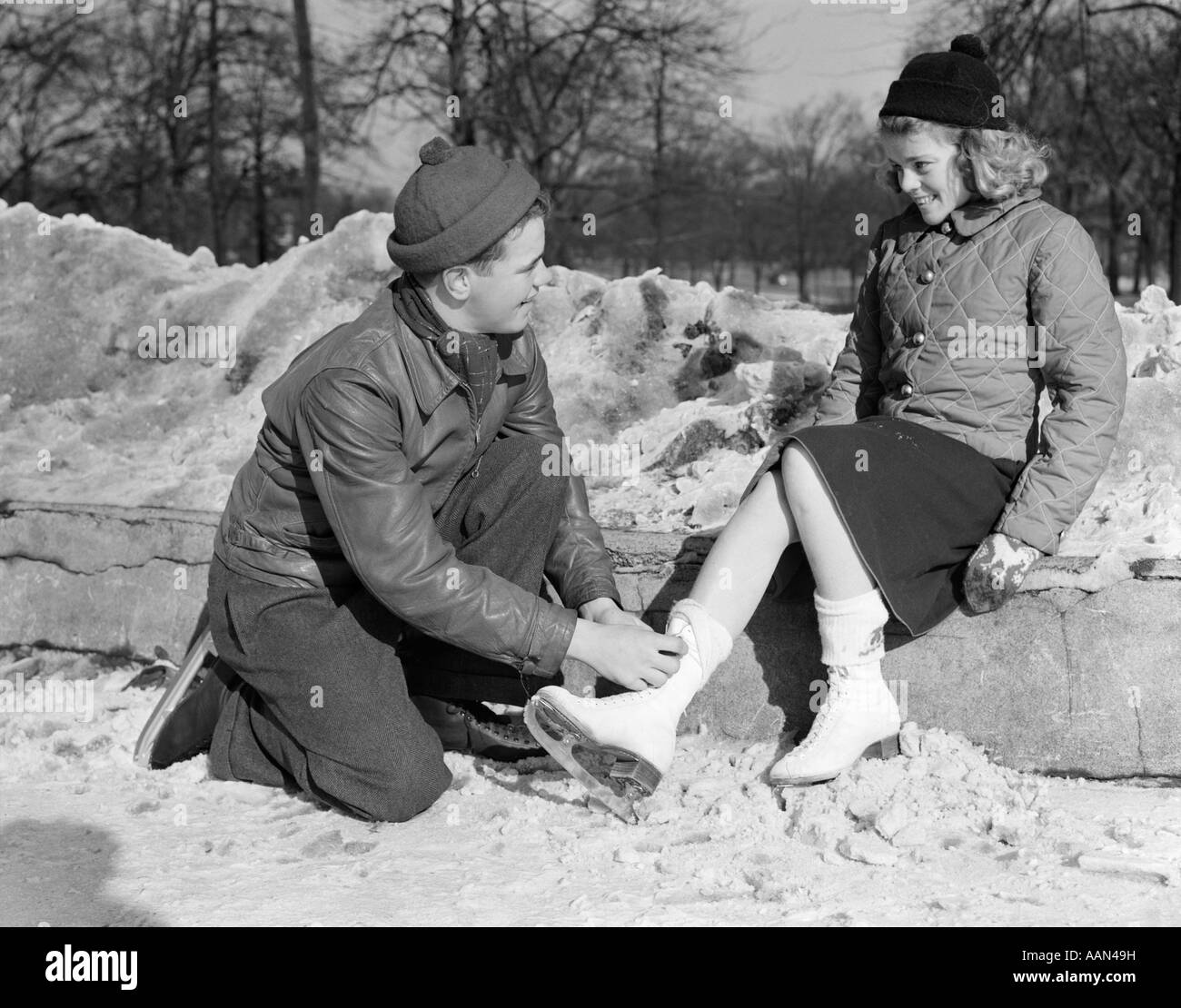 1930s 1940s TEENAGE COUPLE IN KNIT CAPS & WINTER JACKETS KNEELING BOY TYING ICE SKATES FOR GIRL - Stock Image