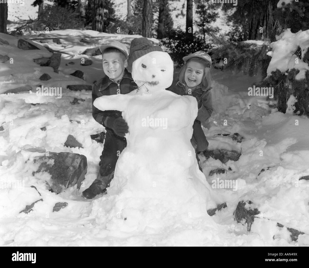 1950s 1960s SMILING BOY AND GIRL BUILDING A SNOWMAN TOGETHER IN SNOWY WOODS - Stock Image