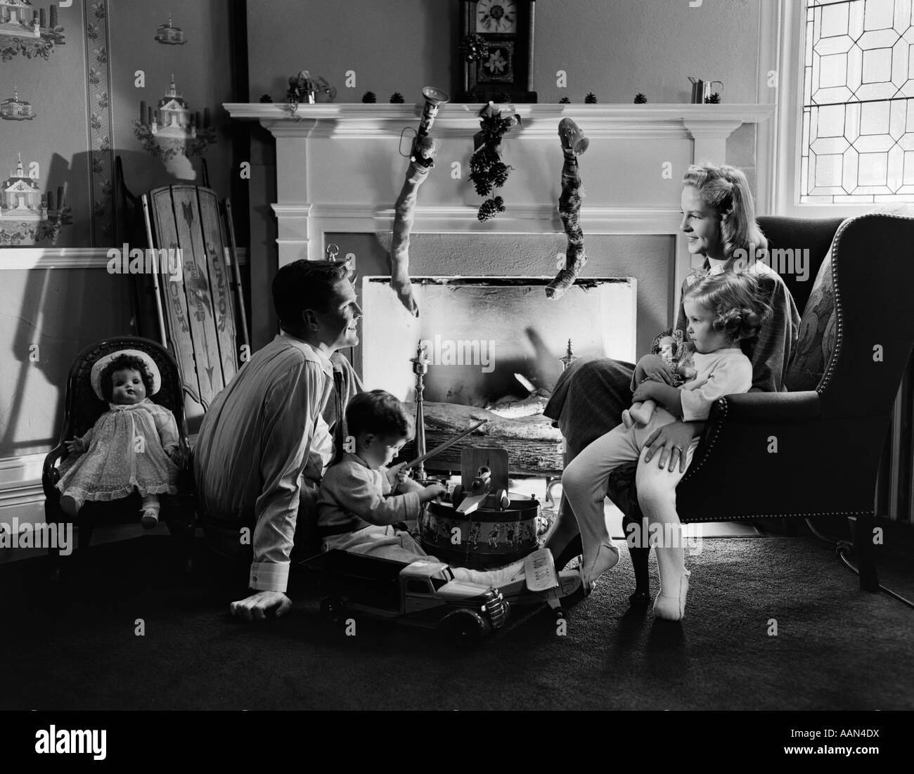 1940s FAMILY SEATED AROUND FIREPLACE AT CHRISTMAS TIME CHILDREN PLAYING WITH TOYS - Stock Image