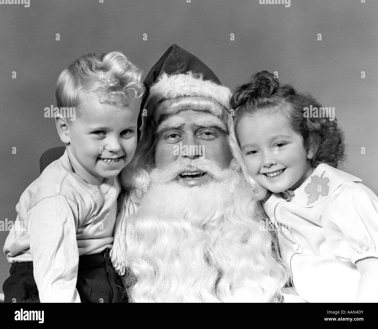 1940s MAN SANTA CLAUS POSING WITH YOUNG BOY AND GIRL IN LAP SMILING ALL LOOKING AT CAMERA - Stock Image
