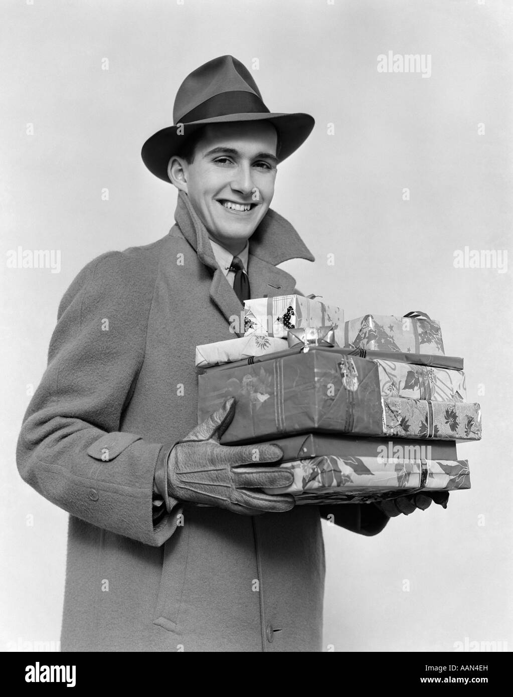 1930s 1940s MAN IN WINTER COAT HAT AND GLOVES HOLDING PILE OF WRAPPED  CHRISTMAS PRESENTS SMILING dc9cdf8497c0
