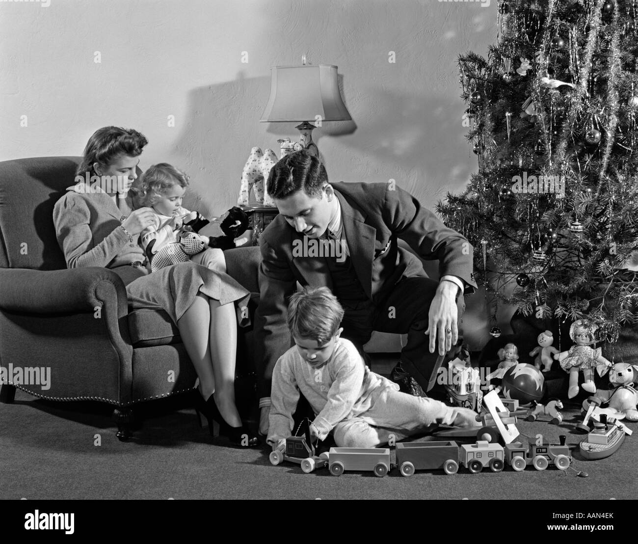1930s 1940s FAMILY AROUND CHRISTMAS TREE BOY PLAYING WITH TRAIN DAD HELPING MOM AND GIRL IN CHAIR - Stock Image