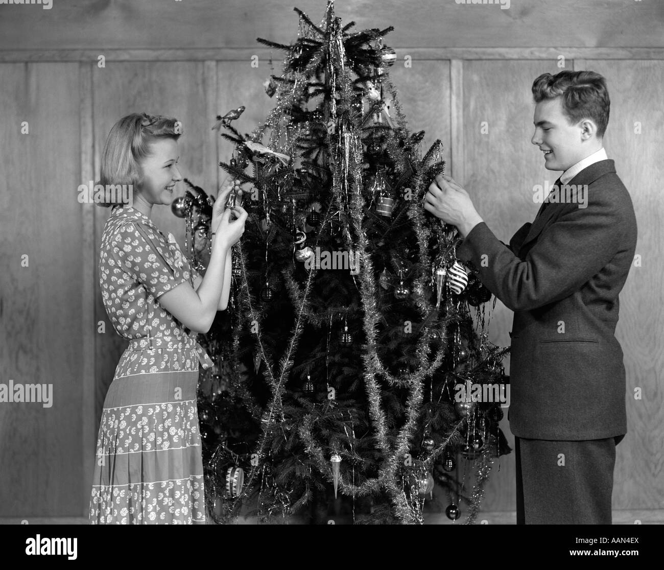 1940s couple decorating christmas tree with tinsel and ornaments